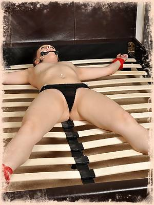 Tight slut stretched on a bed in bondage